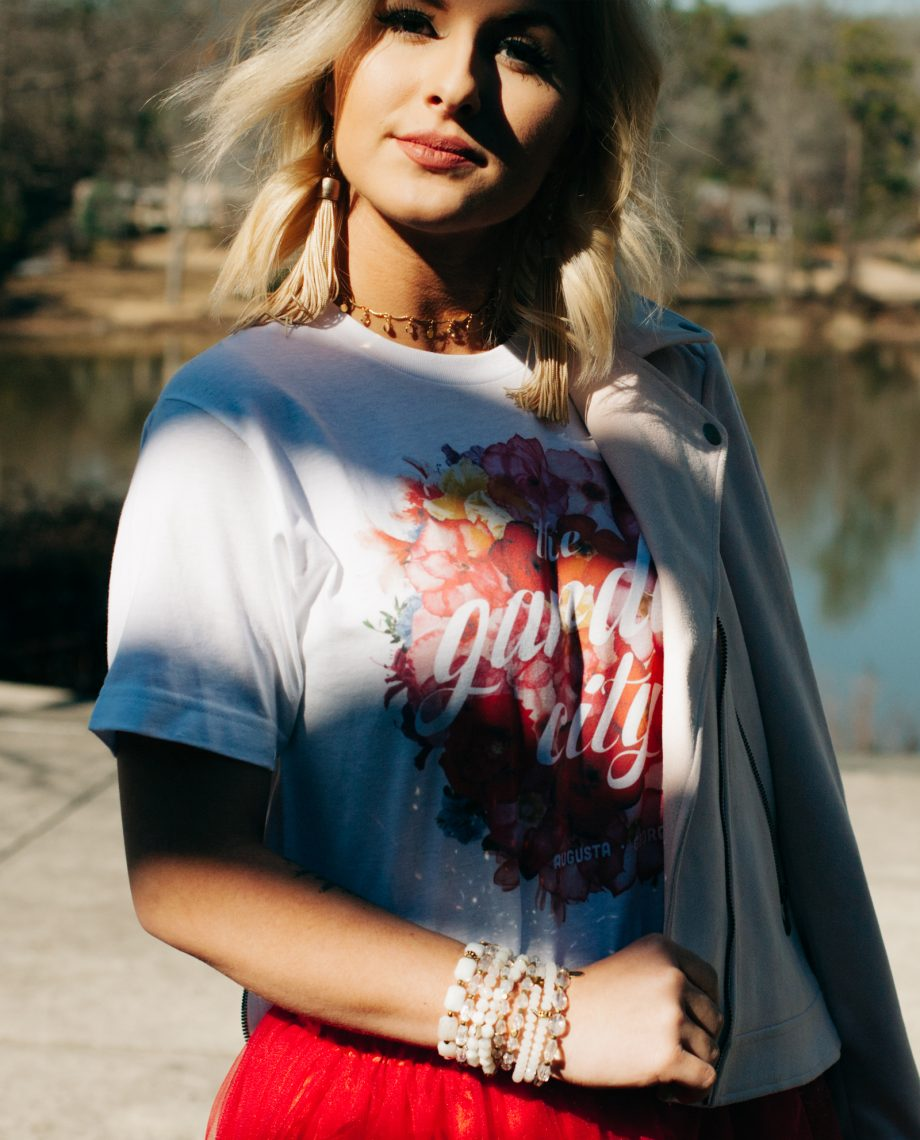 Woman wearing white Floral Garden City shirt with red skirt and jacket