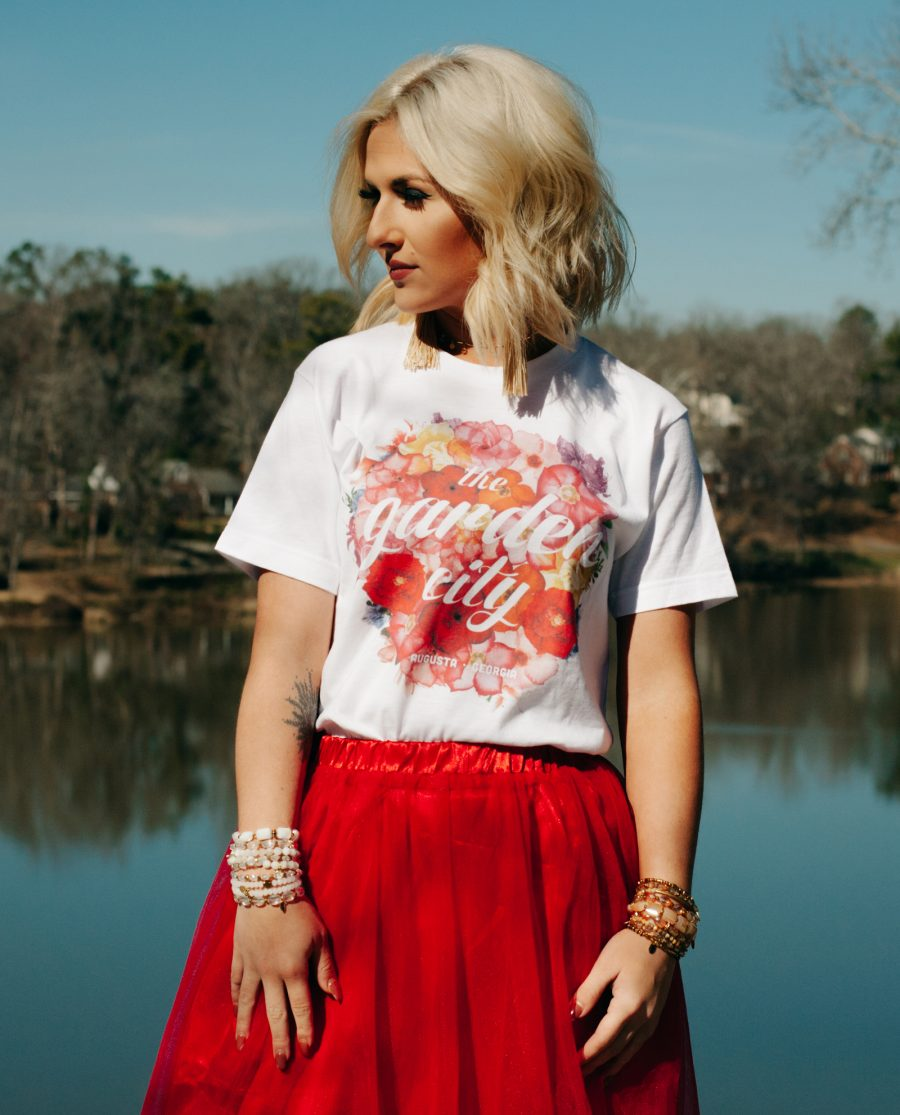 Woman by the water wearing floral Garden City shirt with red skirt