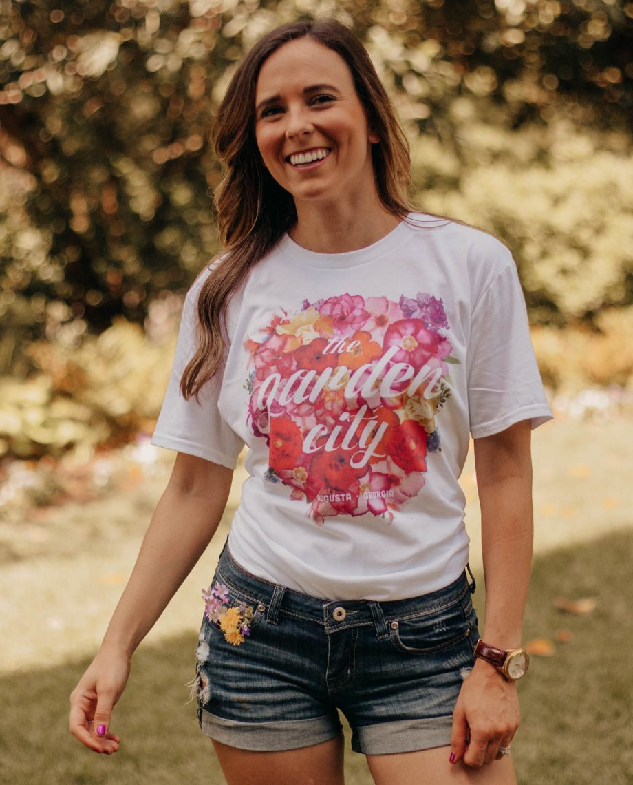 Woman wearing white Floral Garden City shirt with denim shorts