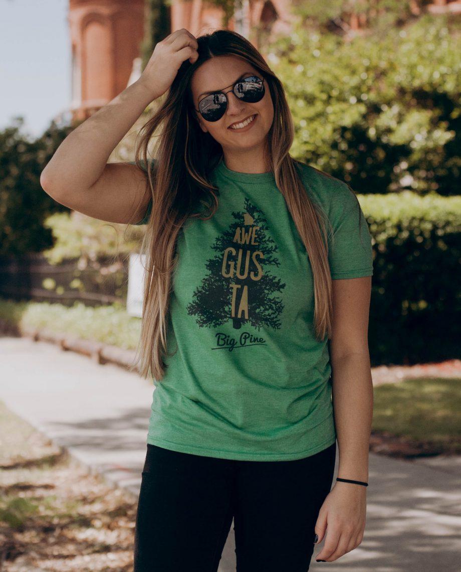 Woman in sunglasses wearing green Awe Gus Ta shirt