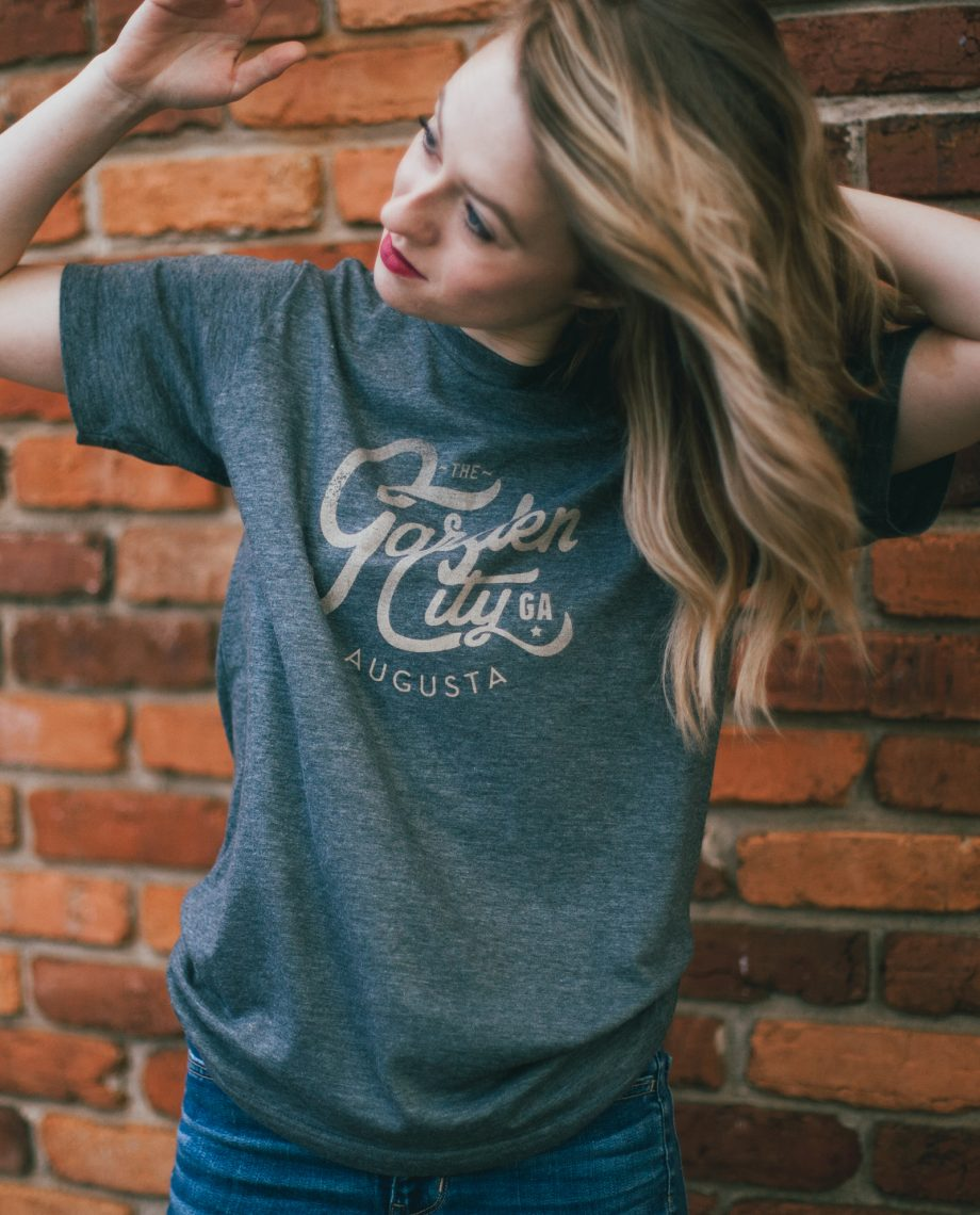 Woman in front of brick wall wearing blue vintage Garden City shirt