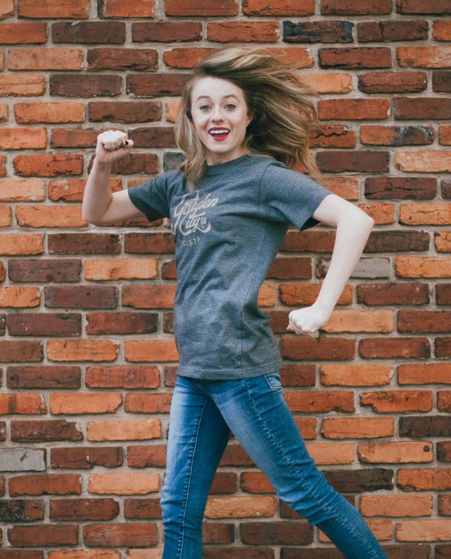 Woman jumping in front of a brick wall wearing blue vintage Garden City shirt
