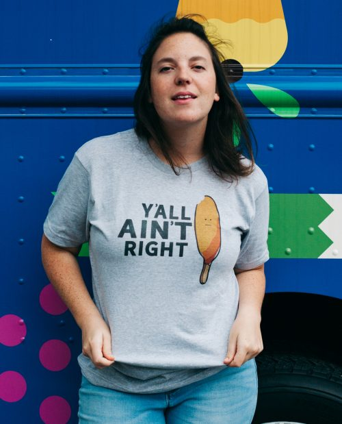 Woman in front of blue truck and wearing gray Y'all Ain't Right shirt