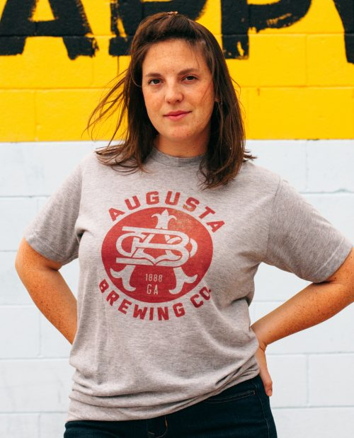 Woman with hands on hips wearing Augusta Brewing shirt