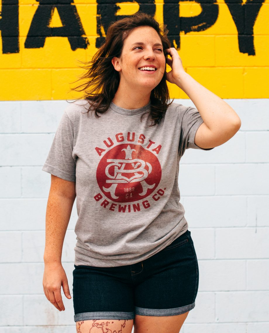 Woman in front of Happy mural wearing gray Augusta Brewing shirt