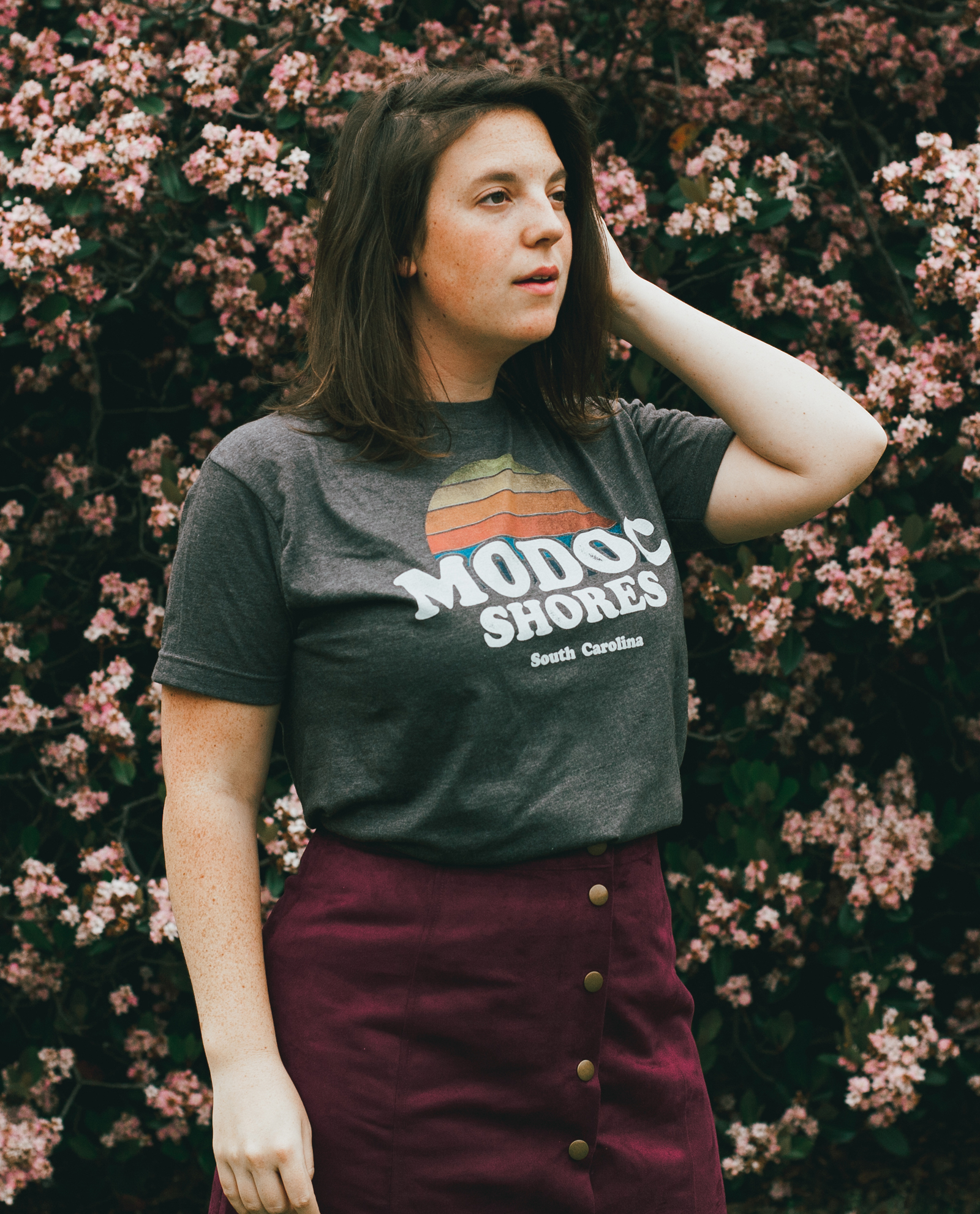 Woman in front of flowers wearing Modoc Shores shirt