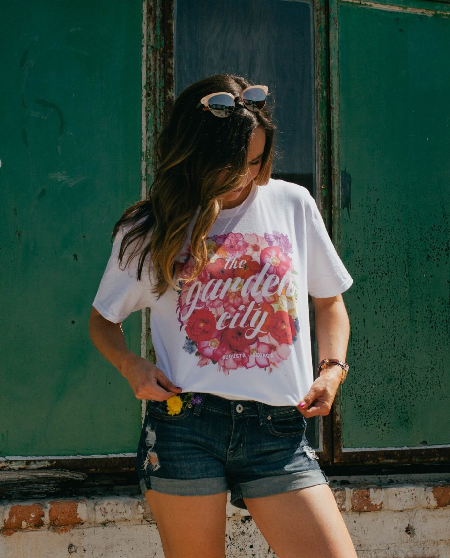 Woman with sunglasses on her head wearing the Floral Garden City shirt with denim shorts