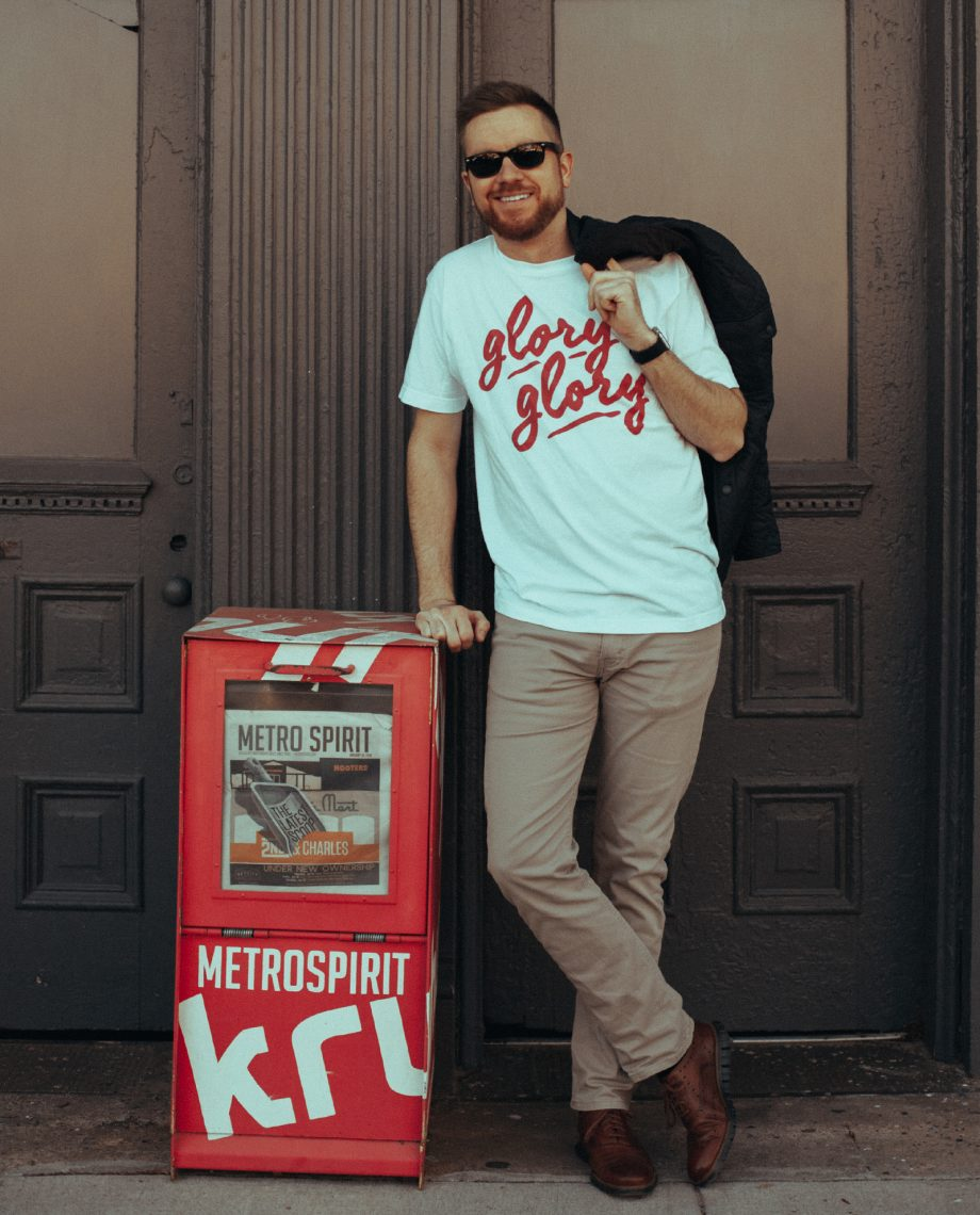Man leaning on newspaper box wearing white Glory Glory shirt with jacket over shoulder