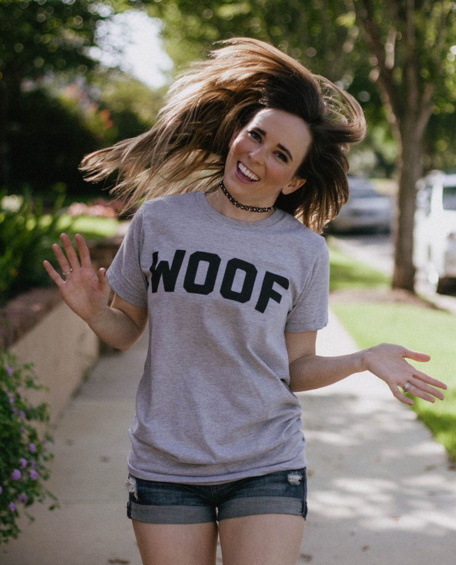 Woman flipping hair and wearing gray WOOF shirt