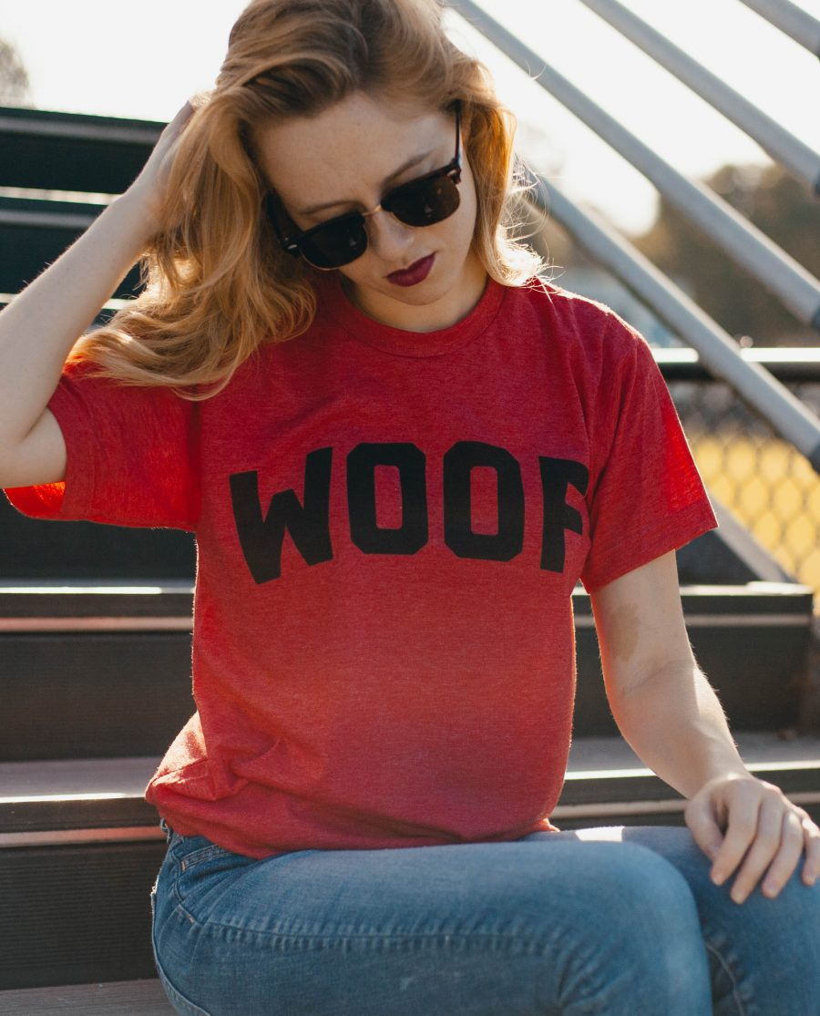 Woman in sunglasses sitting on steps and wearing red WOOF shirt