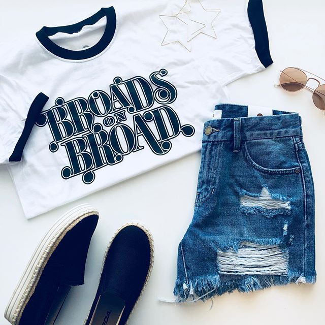 Flatlay with Broads on Broad shirt and denim shorts