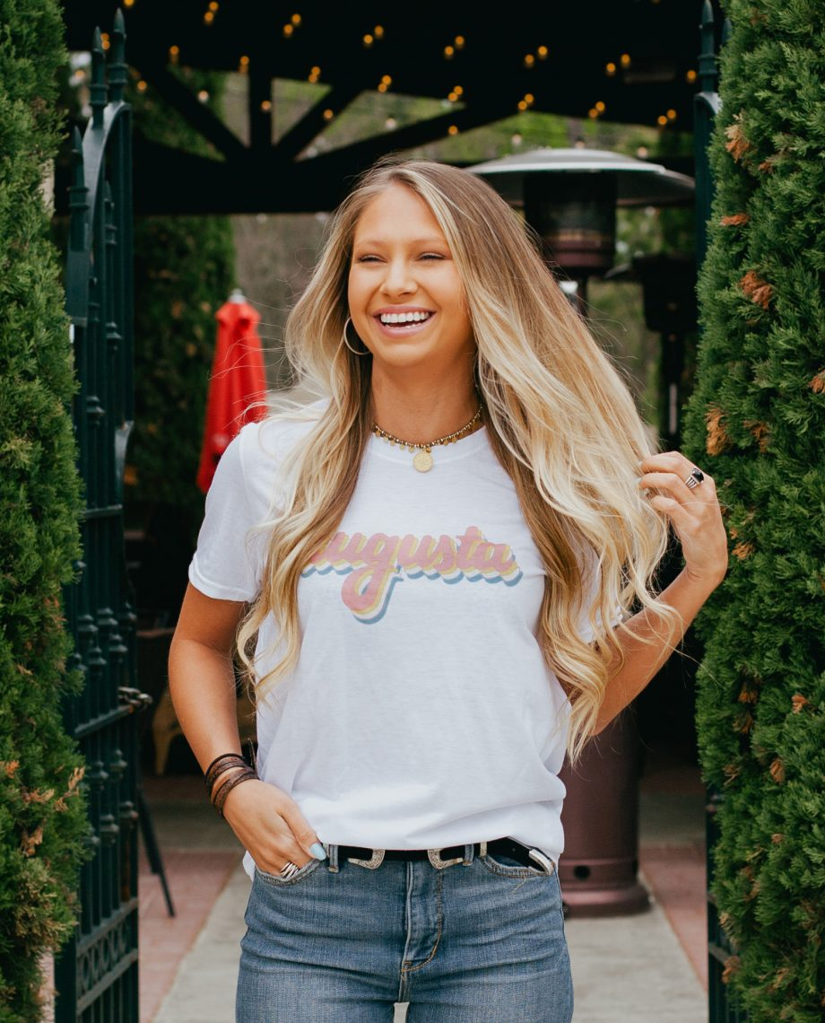 Woman in front of gate entrance wearing white Retro Augusta shirt with jeans