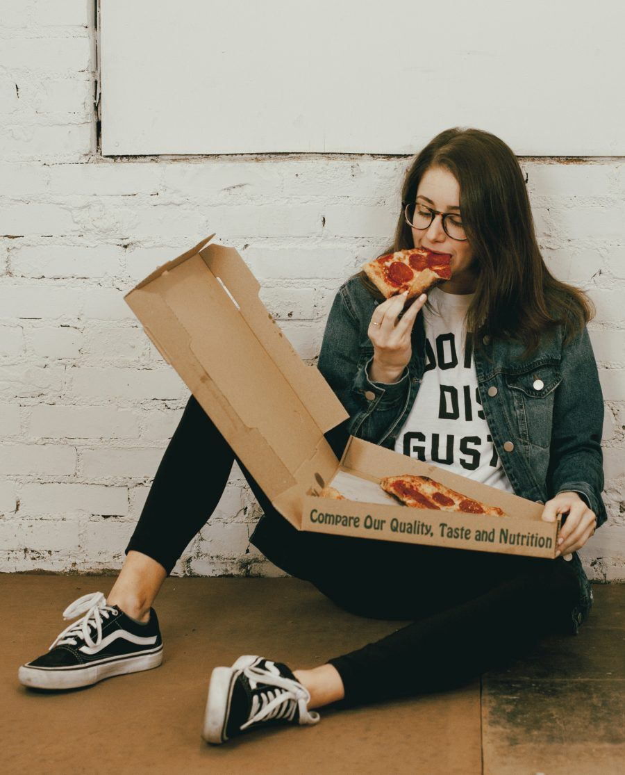 Woman sitting on the floor eating pizza and wearing a white Don't Dis Gusta shirt
