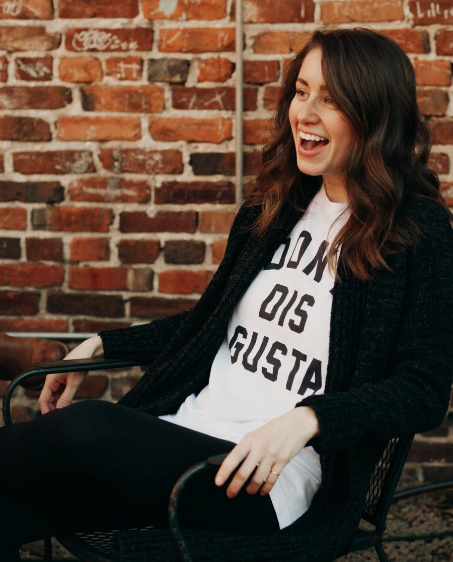 Woman sitting in front of a brick wall wearing a white Don't Dis Gusta shirt