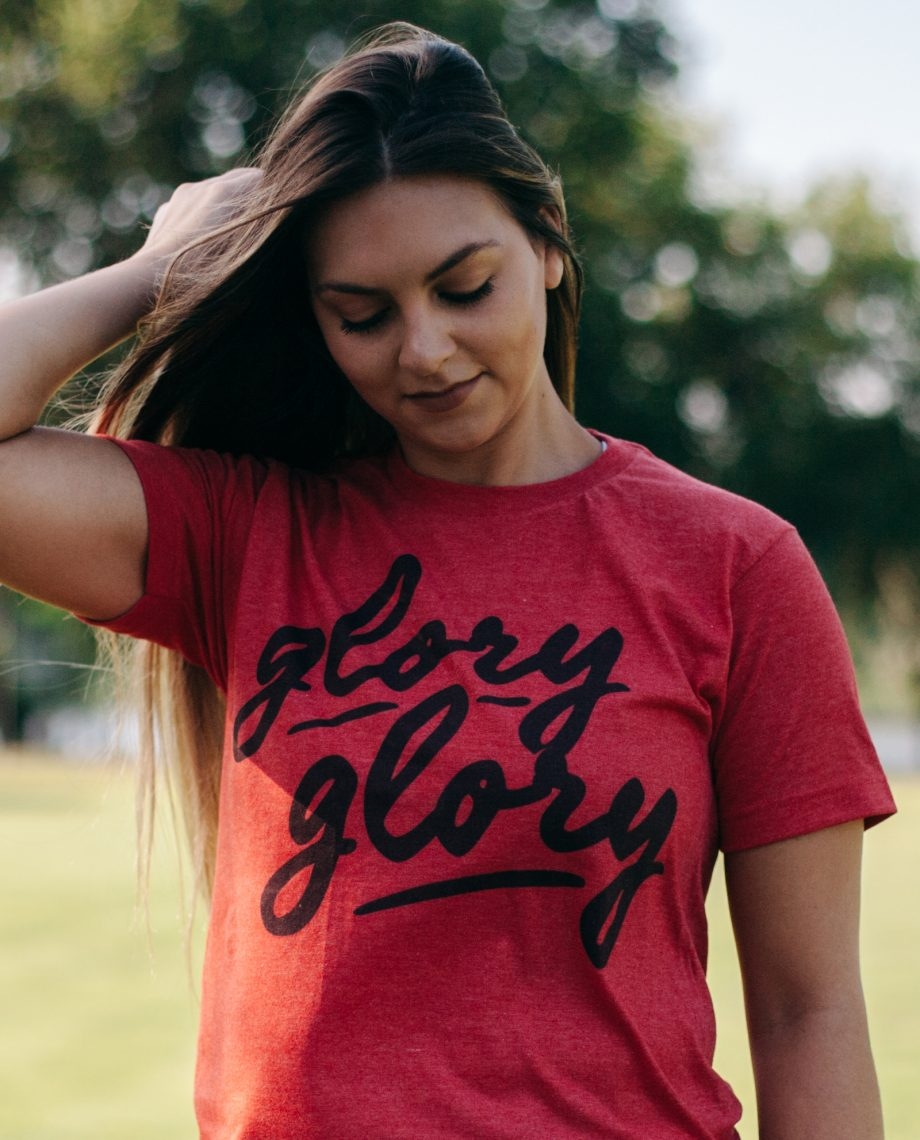 Woman wearing red Glory Glory shirt with hand in her hair