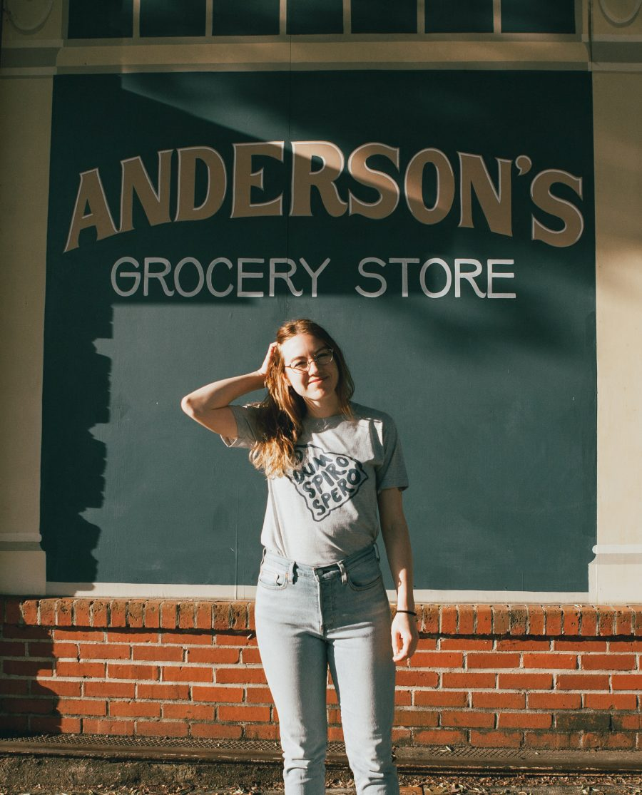 Woman in front of Anderson's Grocery wearing gray Dum Spiro Spero