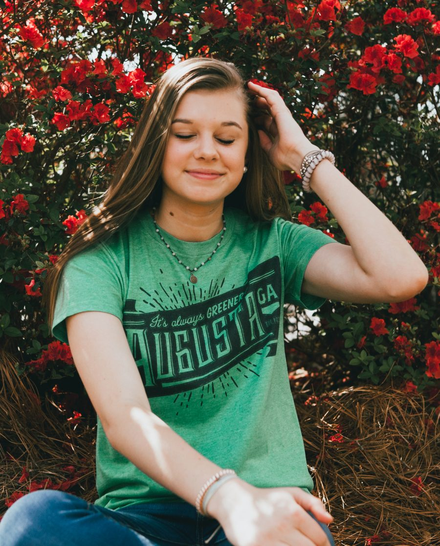 Girl sitting in front of flowers with eyes closed and wearing Always Greener shirt
