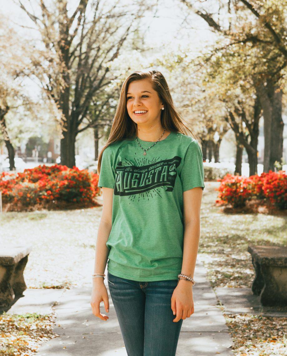 Girl wearing green Always Greener shirt on sidewalk in front of flowers
