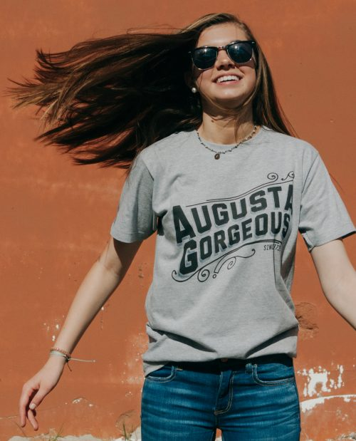 Girl in sunglasses with hair flying wearing gray Augusta Gorgeous shirt