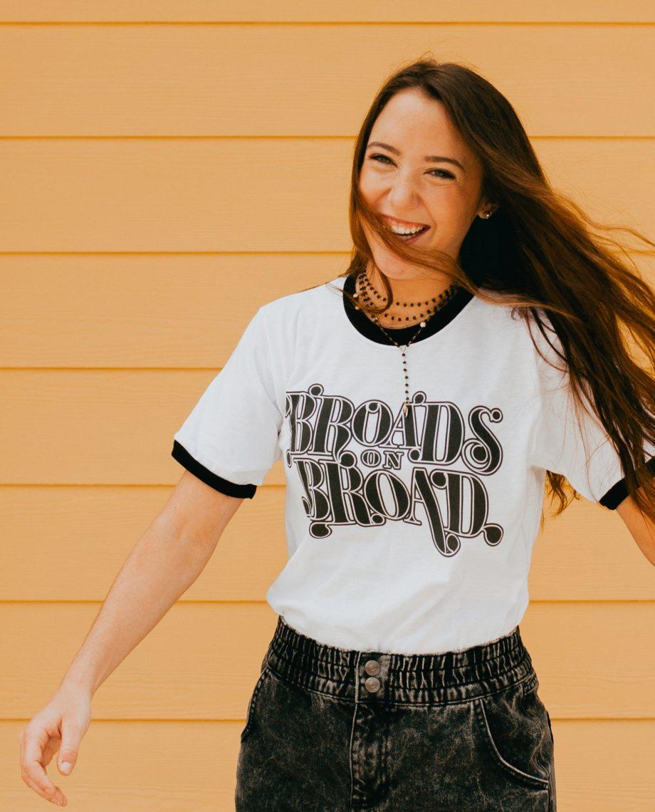 Woman with windblown hair wearing Broads on Broad shirt
