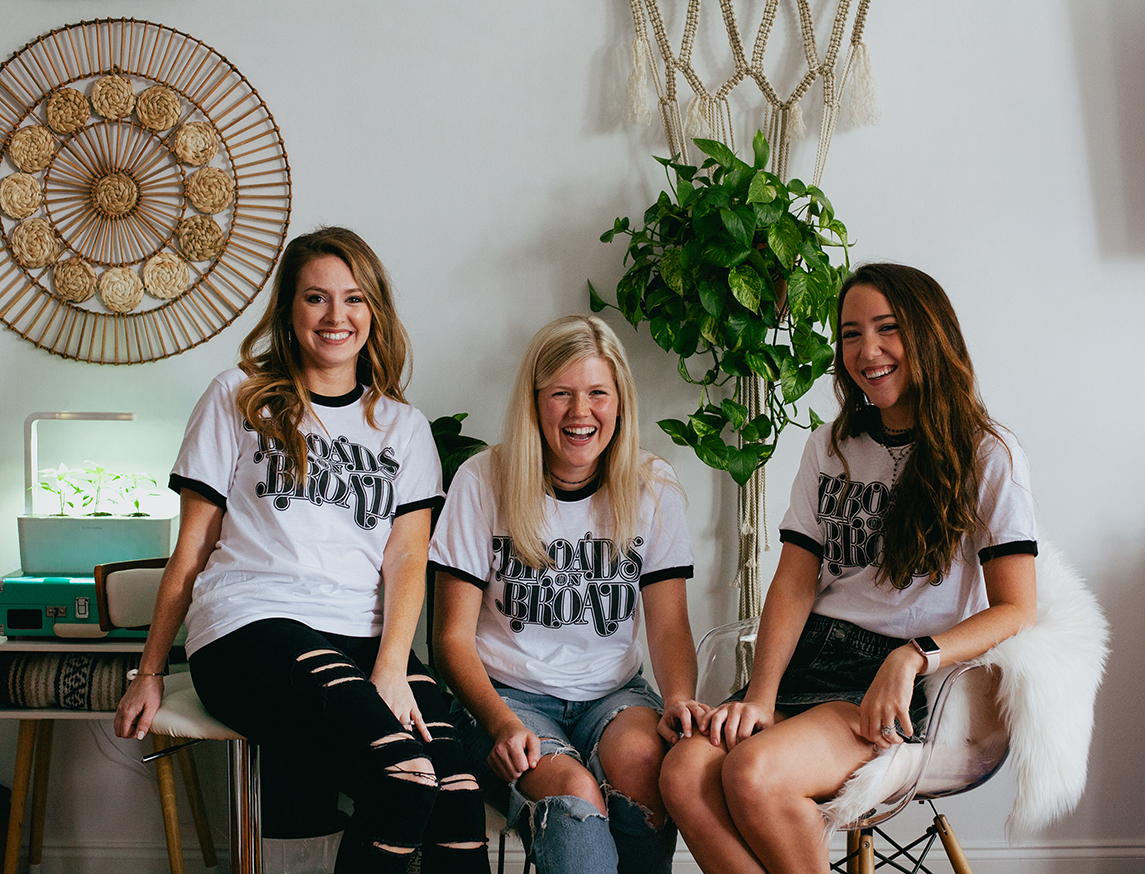Three women sitting in chairs wearing Broads on Broad shirts