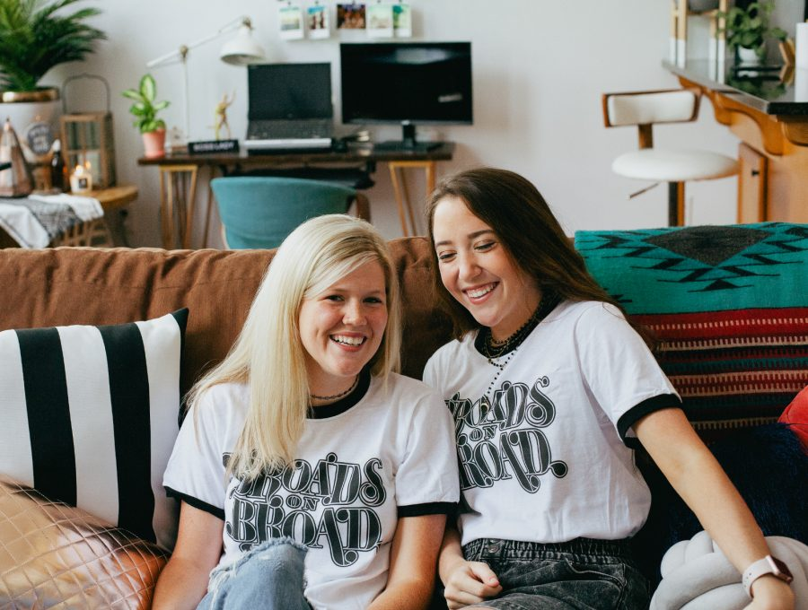 Two women sitting on a couch and wearing Broads on Broad shirts