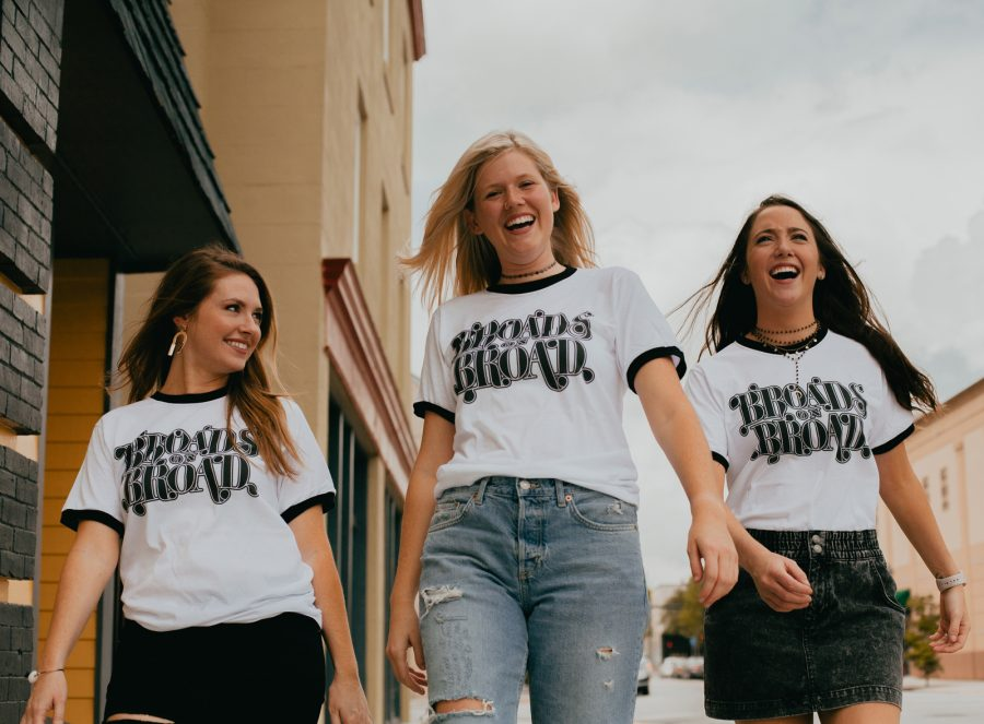 Three women walking and wearing Broads on Broad shirts