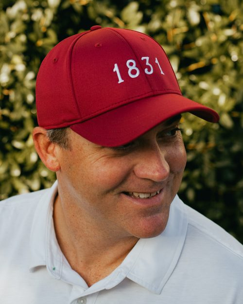 Man wearing crimson and white 1831 Tuscaloosa Alabama feather fit hat