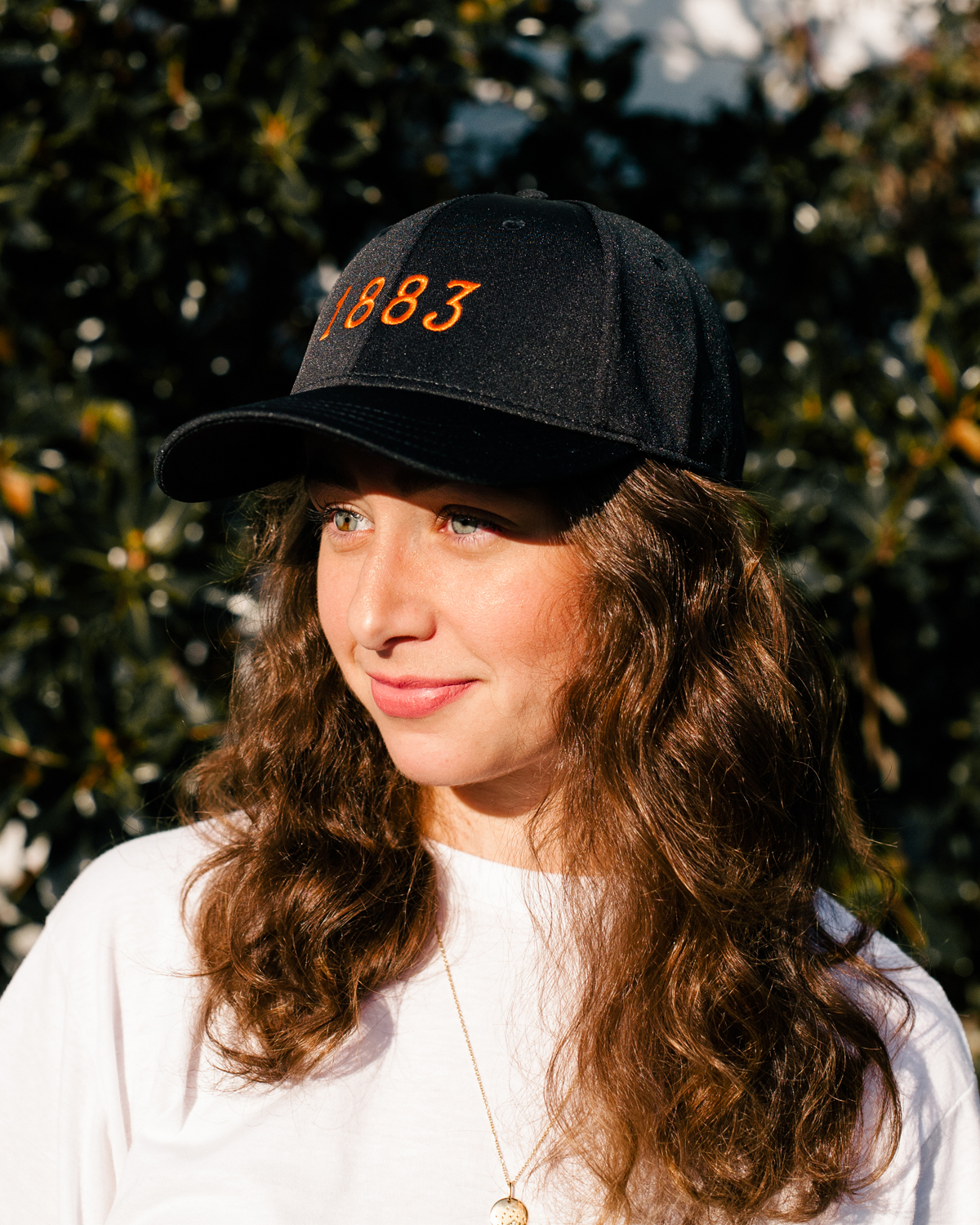 Woman wearing black and orange 1883 Austin Texas feather fit hat