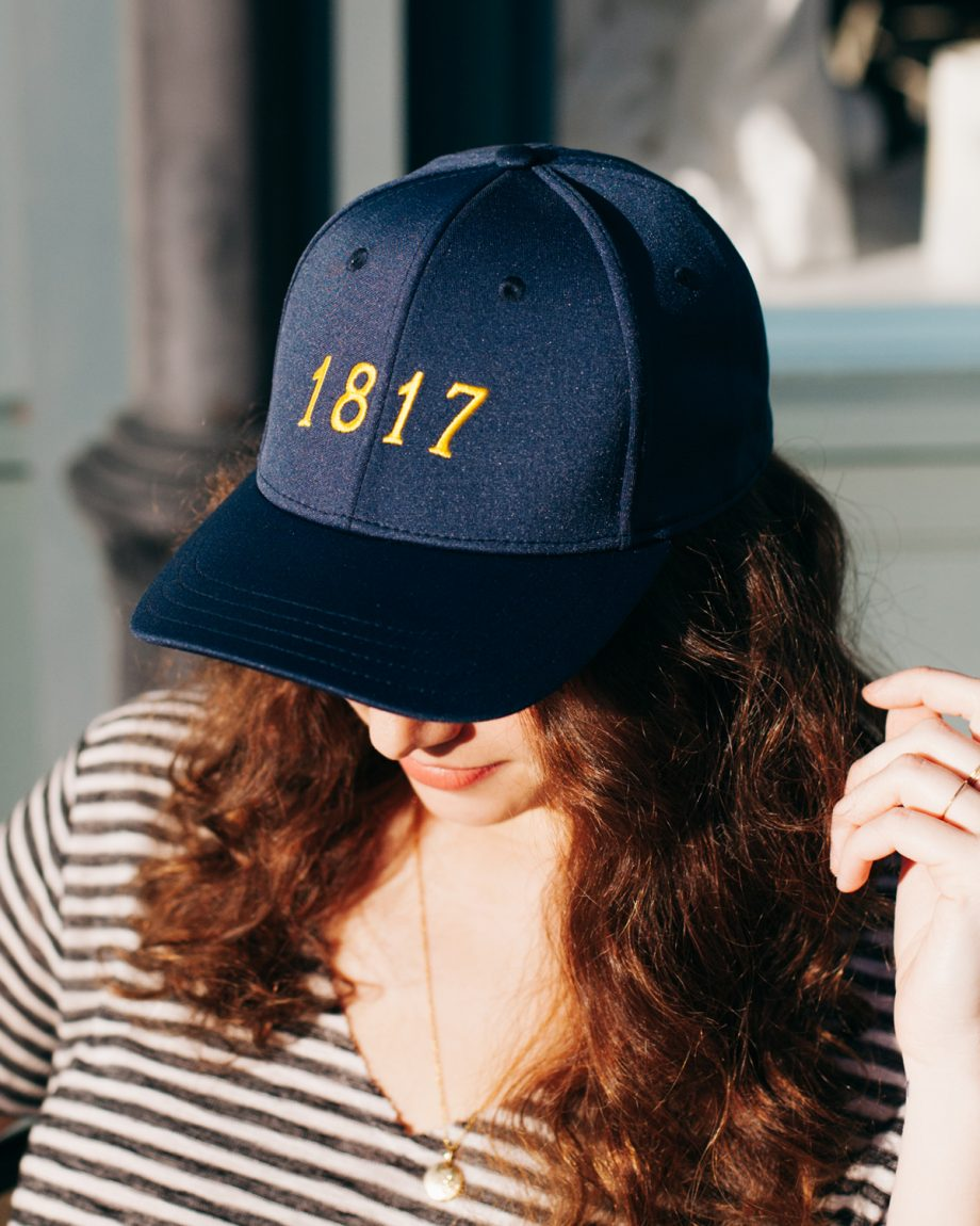 Woman wearing navy and yellow 1817 Ann Arbor Michigan feather fit hat