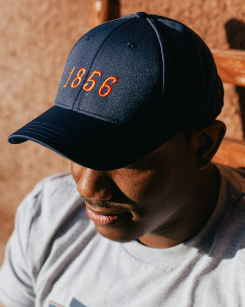 Man wearing navy and orange 1856 Auburn Alabama feather fit hat