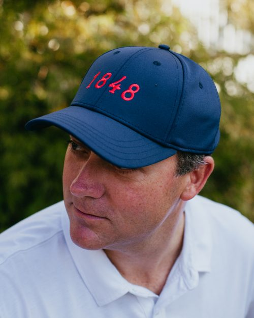 Man wearing navy and red Oxford Mississippi feather fit hat