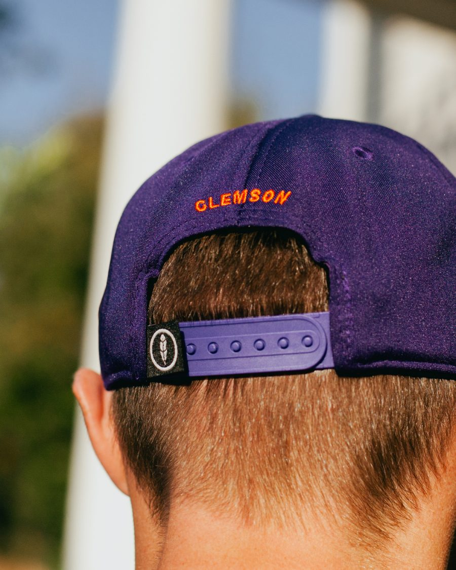 Man wearing purple and orange 1883 Clemson South Carolina feather fit hat