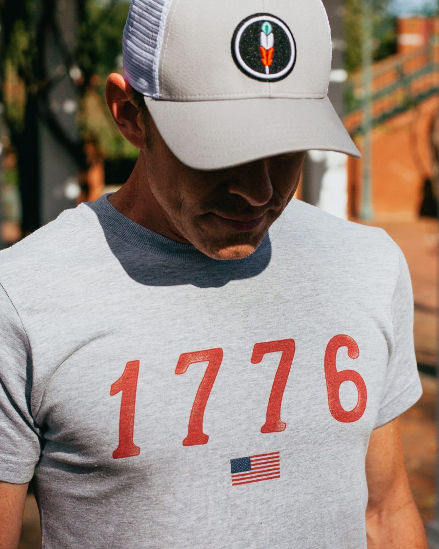 Man wearing gray 1776 USA shirt and gray feather hat