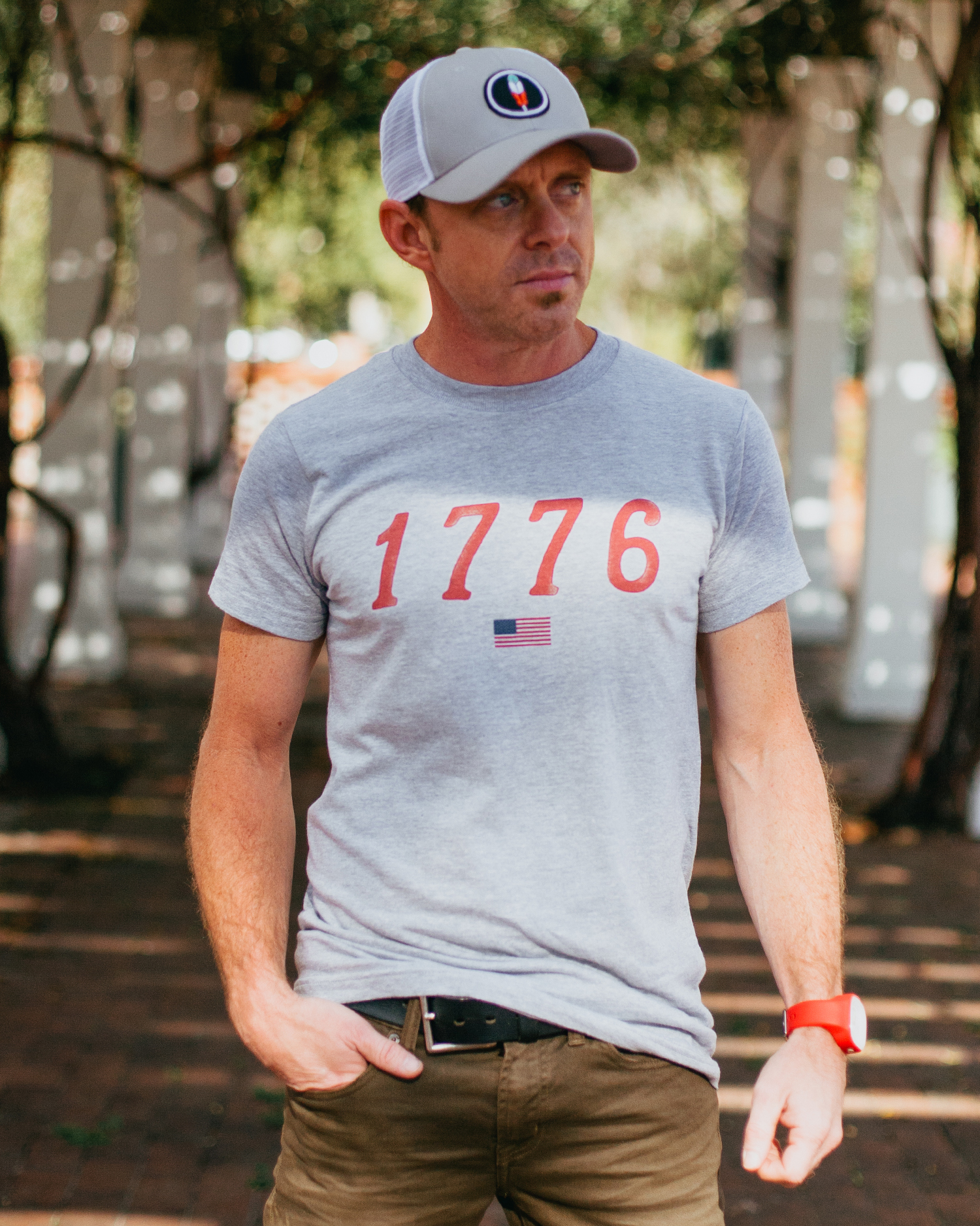 Man wearing gray 1776 USA shirt with gray feather trucker hat