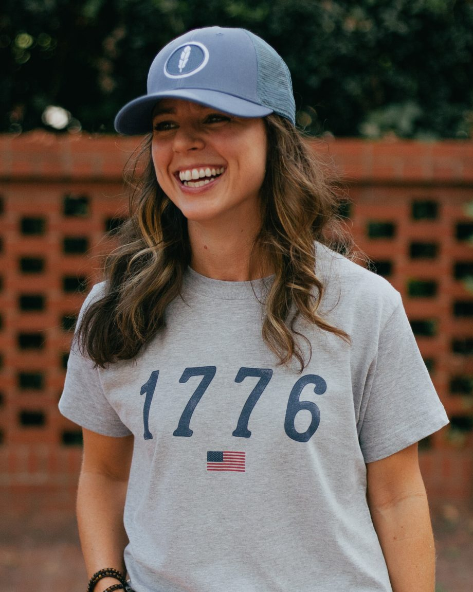 Woman wearing gray 1776 USA shirt with blue feather trucker hat