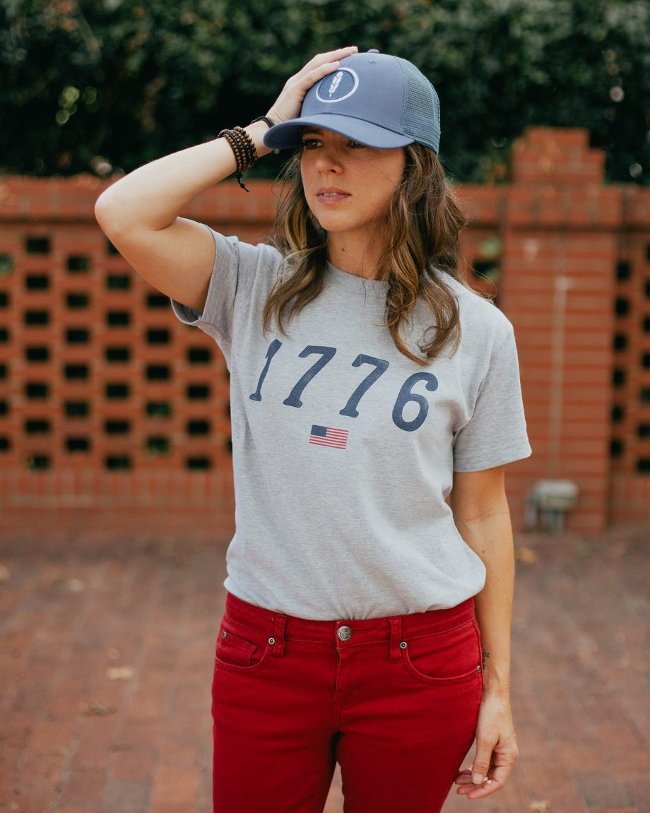 Woman wearing gray 1776 USA shirt with hand on blue feather trucker hat