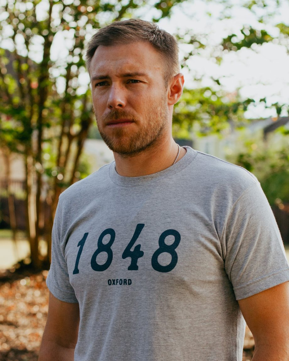 Man wearing gray 1848 Oxford Mississippi shirt