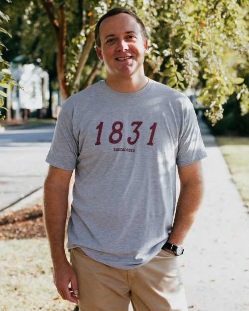 Man wearing gray 1831 Tuscaloosa Alabama shirt shirt and khakis