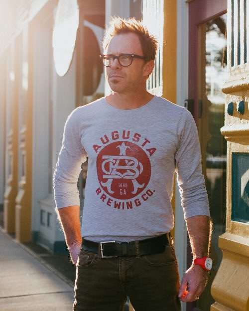 Man wearing gray long sleeve Augusta Brewing shirt