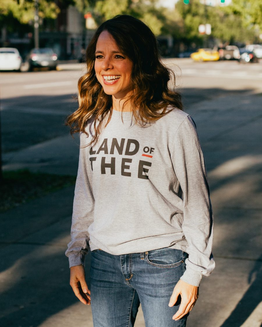 Woman wearing gray long sleeve Land of Thee shirt with jeans