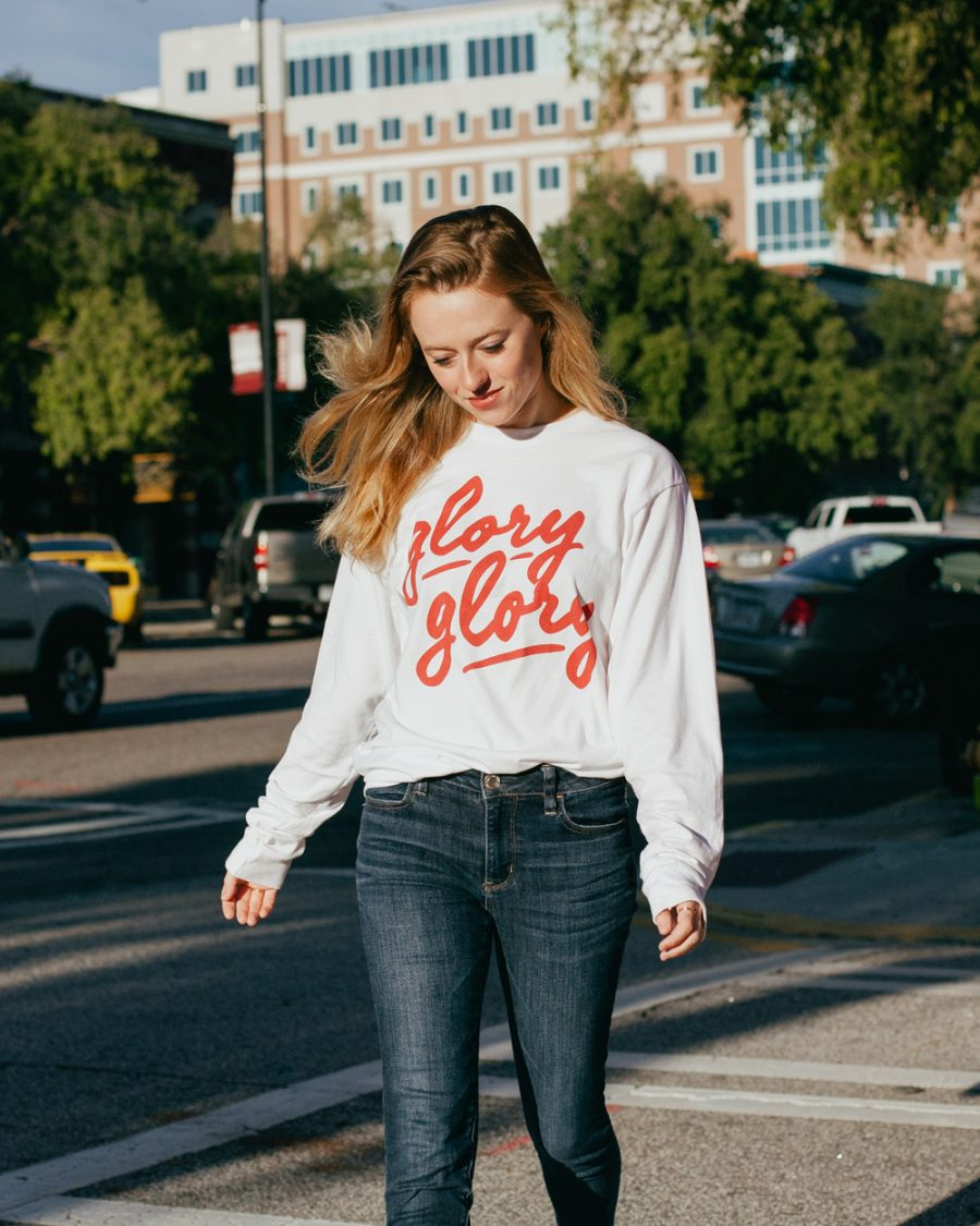 Woman wearing white long sleeve Glory Glory shirt with jeans
