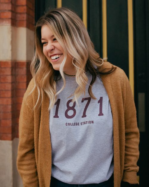 Woman wearing gray 1871 College Station Texas shirt with yellow sweater