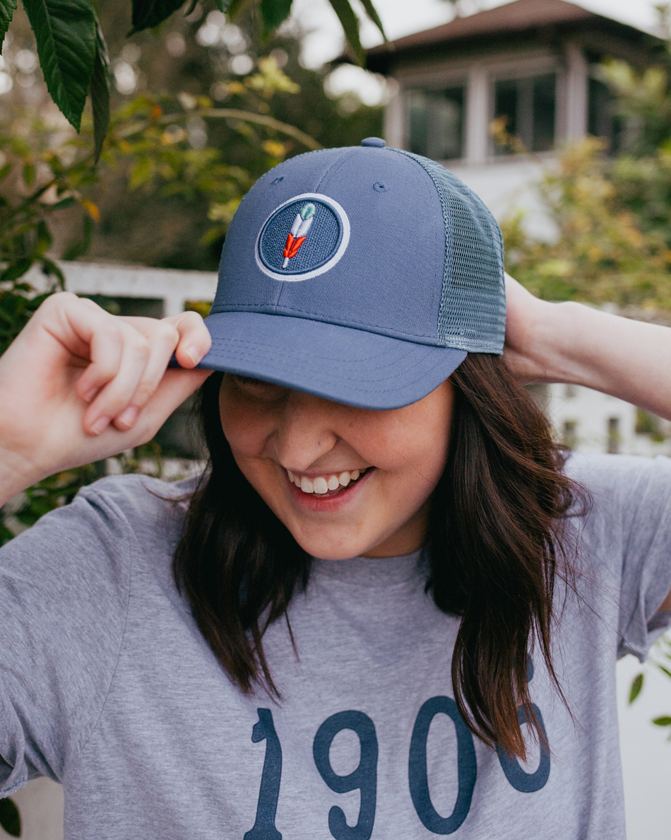 68041b77db5fd2 Woman wearing blue Land of Thee feather trucker hat