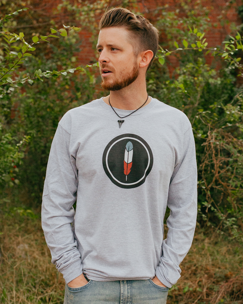 Man wearing gray long sleeve Land of Thee feather shirt with jeans