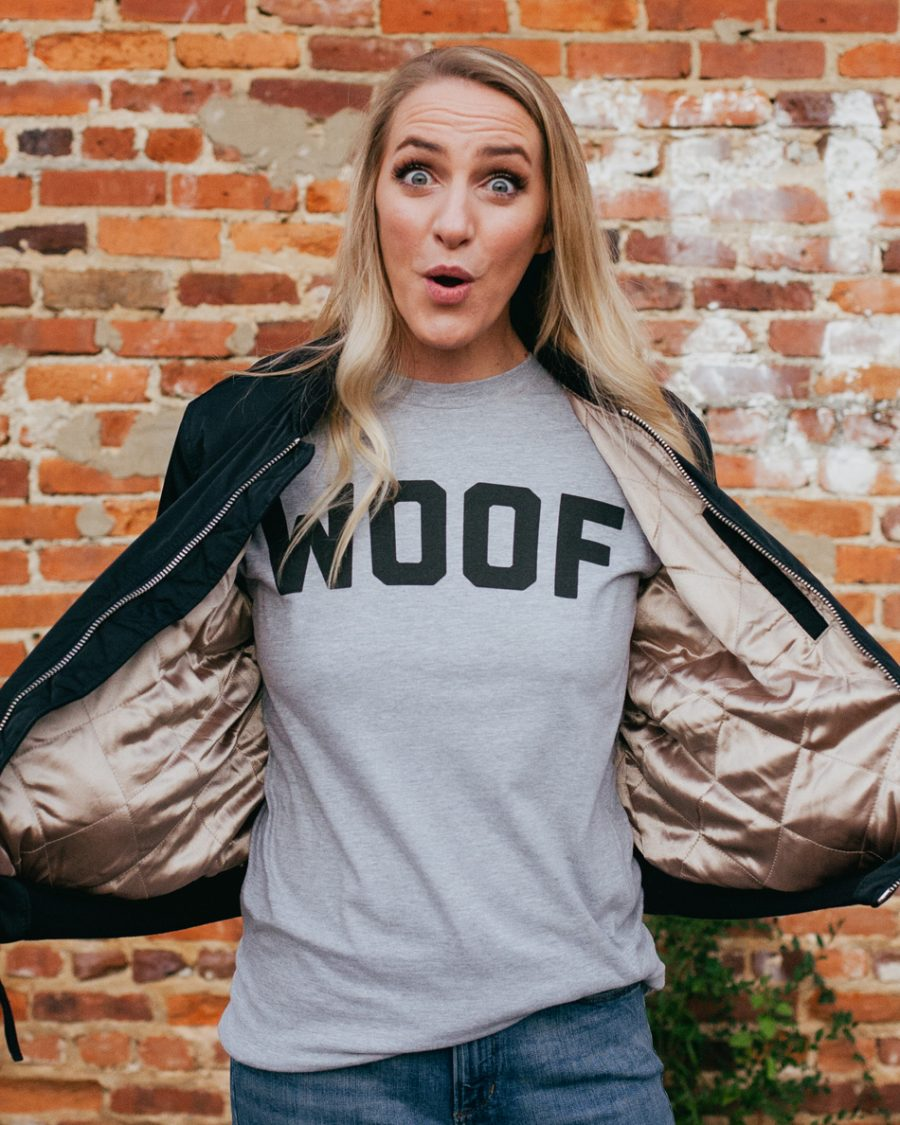 Woman wearing gray long sleeve WOOF shirt with black jacket and jeans