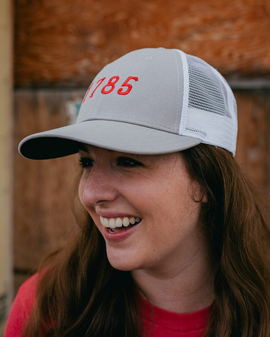 Woman wearing gray and red 1785 Athens Georgia trucker hat