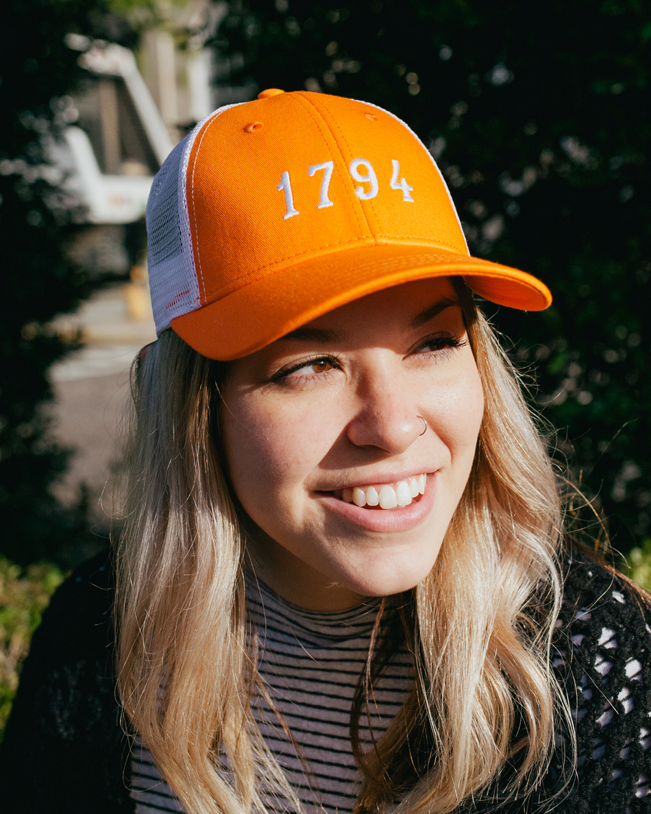 Woman wearing orange and white 1794 Knoxville Tennessee trucker hat