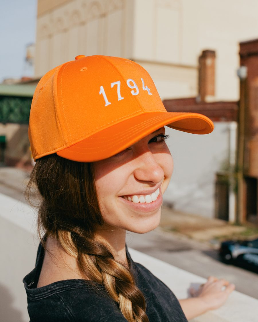 Woman wearing orange 1794 Knoxville Tennessee feather fit hat