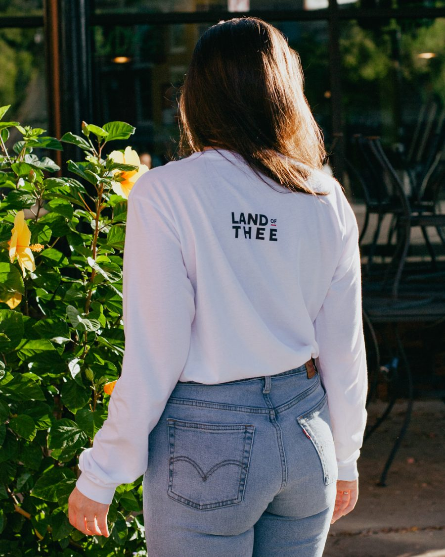 Woman wearing white long sleeve shirt with Land of Thee on the back